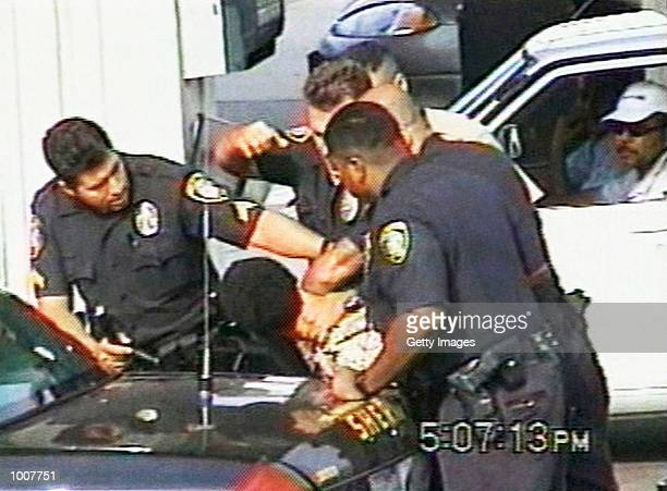 An Inglewood police officer raises his fist while other officers restrain 16yearold Donovan Jackson on July 8 2002 in Inglewood California Jackson...