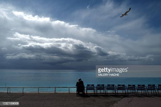 """An inhabitant sits on one of the blue chairs facing the Mediterranean sea, on the """"Promenade des Anglais"""", in the French riviera city of Nice, on..."""