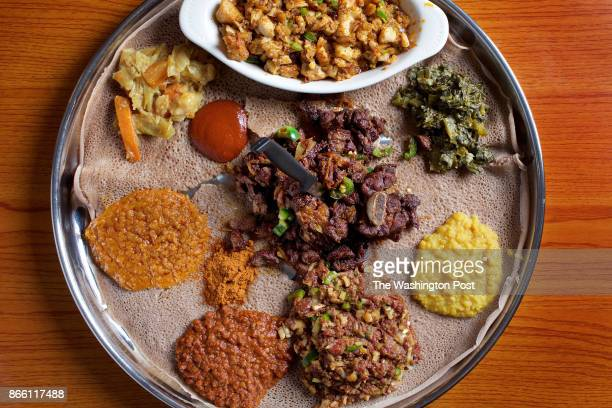 WASHINGTON DC An injeralined platter with entrees Fish Dulet Collard Greens Yellow Split Peas Dulet Red Lentils Chickpeas Carrots and Cabbage and in...