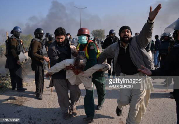 TOPSHOT An injured activist from the TehreekiLabaik Yah Rasool Allah Pakistan religious group is carried away from clashes with police in Islamabad...