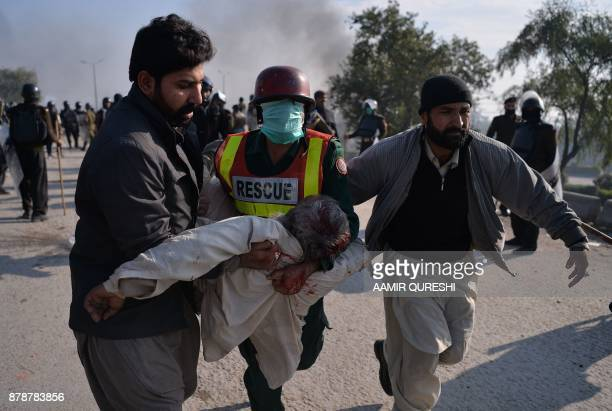 An injured activist from the TehreekiLabaik Yah Rasool Allah Pakistan religious group is carried away from clashes with police in Islamabad on...