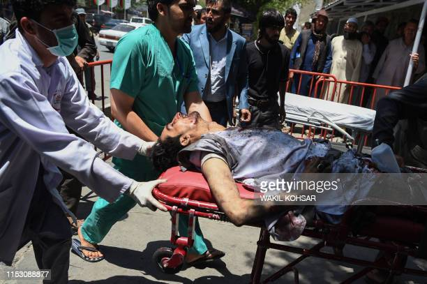 An injured Afghan man is brought on a stretcher to an Italian aid organisation's hospital after a car bomb attack in Kabul on July 1 2019 Dozens of...