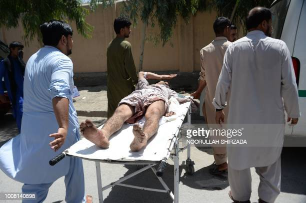 An injured Afghan man is carried on stretcher by voluntaries near the site of suicide attack during an ongoing attack between Afghan security force...