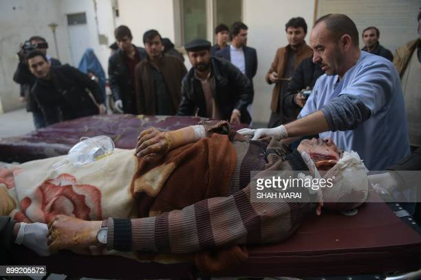 An injured Afghan man is transferred from an ambulance to a hospital following blasts at a Shiite cultural centre in Kabul on December 28 2017 At...