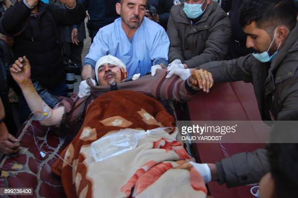 An injured Afghan man is transferred from an ambulance to a hospital following blasts at a Shiite cultural centre in Kabul on December 28 2017 Around...