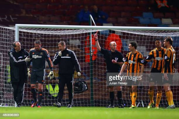 An injured Allan McGregor of Hull City is shown a red card by Referee Mike Dean during the Barclays Premier League match between West Ham United and...