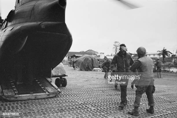 An injured American serviceman prepares to board a transport helicopter at a forward command post in the city of Hu during the Battle of Hu Vietnam...
