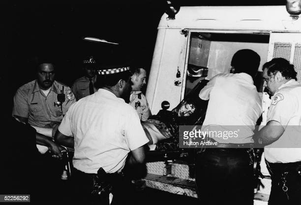 An injured and bloodied protestor lying on stretcher is loaded into the back of an ambulance by Chicago police officers during the riots that erupted...