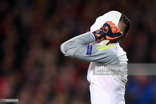 An injured Anthony Lopes of Olympique Lyonnais reacts as he leaves the pitch during the UEFA Champions League Round of 16 Second Leg match between FC...