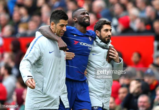 An injured Antonio Ruediger of Chelsea is given assistance during the Premier League match between Manchester United and Chelsea FC at Old Trafford...