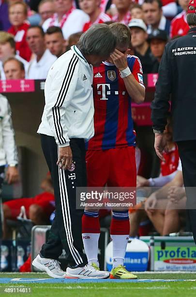An injured Bastian Schweinsteiger of Bayern Muenchen talks to team doctor HansWilhelm MuellerWohlfahrt as he is substituted during the Bundesliga...