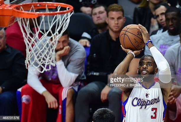 An injured Blake Griffin in street clothes watches from the bench as teammate Chris Paul of the Los Angeles Clippers shoots against the Houston...