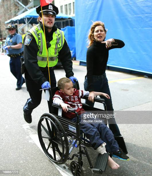 An injured boy is pushed in a wheelchair by a Boston police officer at the scene of the first explosion near the finish line of the Boston Marathon.