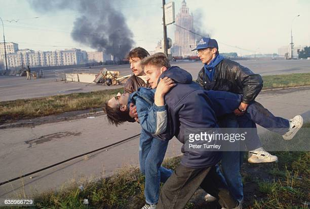 An injured civilian is carried away during the siege on the Russian Parliament in which ProYeltsin forces fired on the parliament building in order...