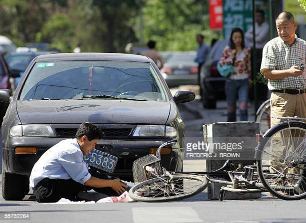 An injured cyclist reacts in pain after a collision with a vehicle along a Beijing street 21 September 2005 as the driver prepares to make a phone...