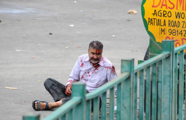 An injured Dera follower sitting on road during clash after in after the Dera chief verdict at CBI court on August 25 2017 in Panchkula India Gurmeet.