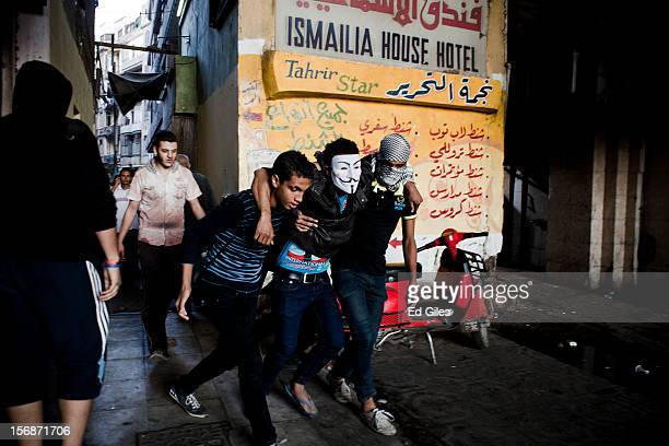 An injured Egyptian protester is helped away from violent clashes between riot police and demonstrators near Tahrir Square on November 23 2012 in...