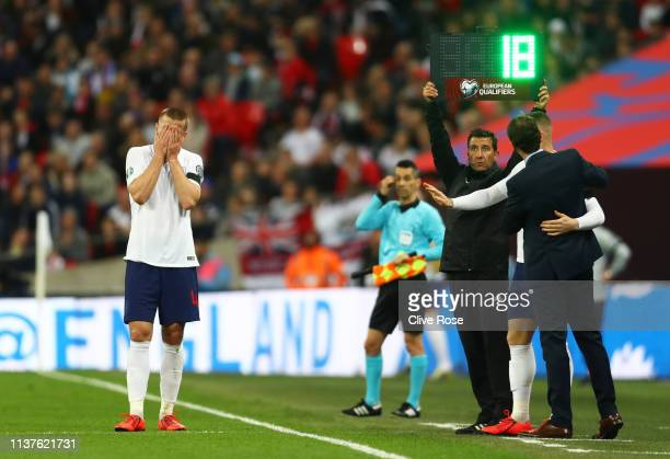 An injured Eric Dier of England reacts as Gareth Southgate manager of England and substitute Ross Barkley look on from the touchline during the 2020...