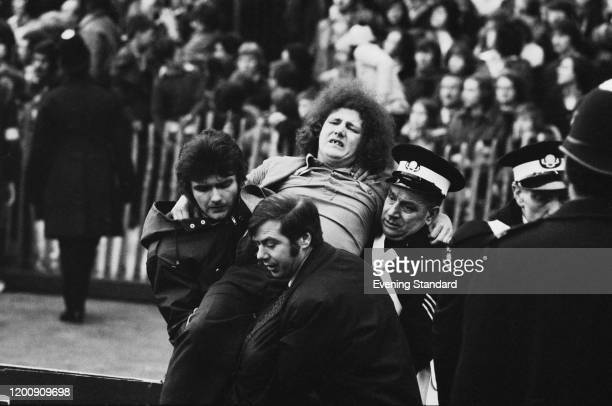 An injured fan is carried by other fans and a St John Ambulance volunteer at the FA Cup Fifth Round match between Chelsea and Crystal Palace at...