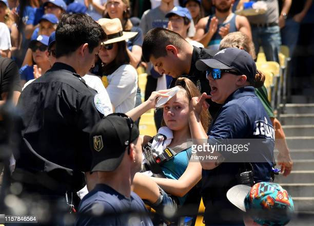 An injured fan is escorted on a stretcher after she was hit by a foul ball off the bat of Cody Bellinger of the Los Angeles Dodgers during the first...
