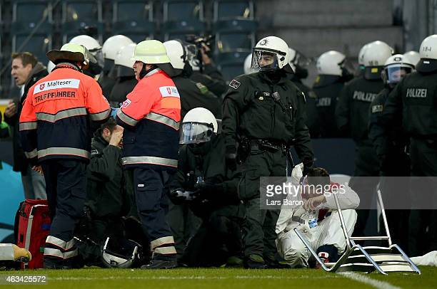 An injured fan of Koeln sits on the pitch next to riot police during the Bundesliga match between Borussia Moenchengladbach and 1 FC Koeln at...