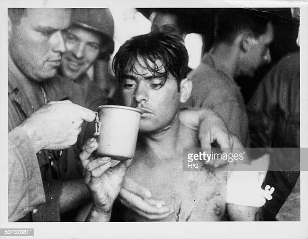 An injured Filipino soldier being treated by US troops following a battle in Ormoc during World War Two Leyte Philippines circa 1943