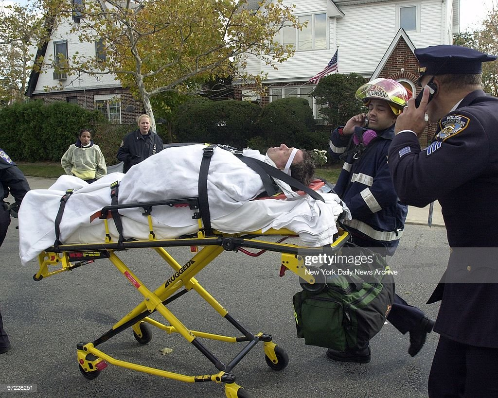 An injured firefighter is rushed to an ambulance in Belle Ha : News Photo