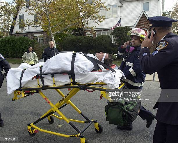 An injured firefighter is rushed to an ambulance in Belle Harbor Queens after responding to the scene of an American Airlines Flight 587 plane crash