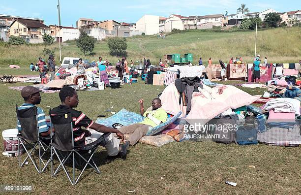 An injured foreign national gestures to his local countrymen at the Chatsworth football grounds south of Durban on April 10, 2015. Hundreds of people...