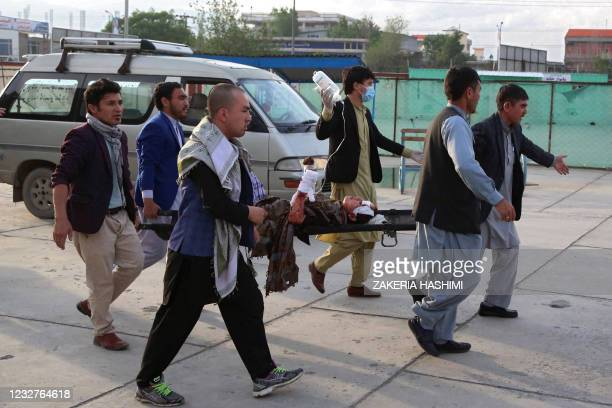 An injured girl is being brought on a stretcher to a hospital following a blast outside a school in the west Kabul district of Dasht-e-Barchi on May...