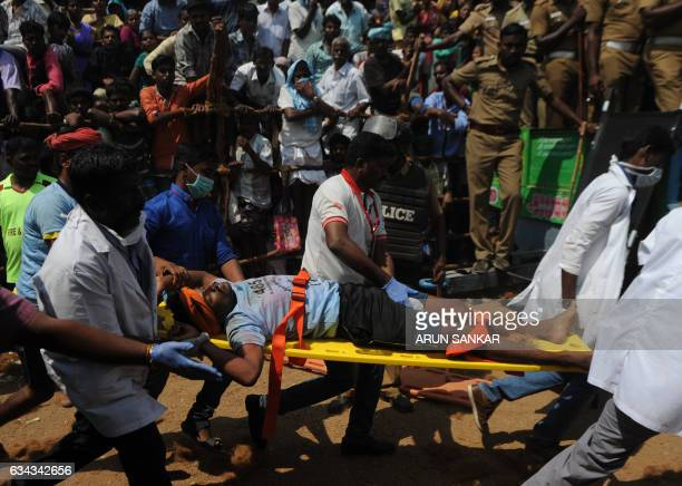 An injured Indian participant in a bullfighting ritual is carried away for treatment during an annual 'Jallikattu' bulltaming in the village of...