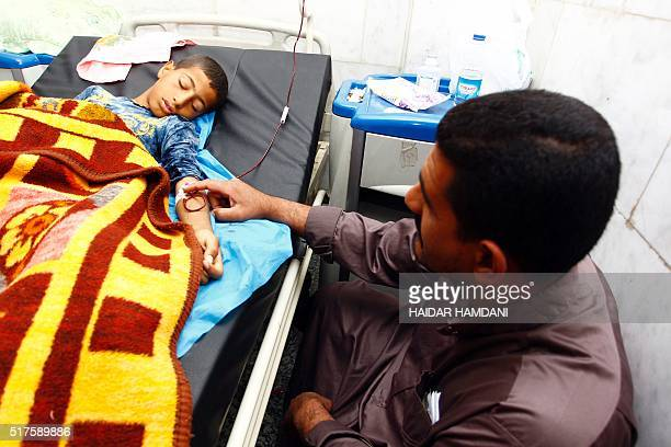 An injured Iraqi boy lies in a hospital bed on March 26 2016 in Iskandariyah a town about 40 kilometres south of the capital Baghdad a day after a...