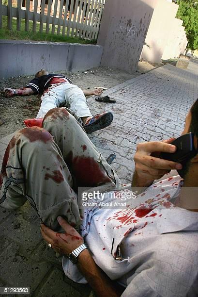 An injured Iraqi civilian calls for an ambulance on September 12 2004 as Palestinian journalist for AlArabiya TV Mezan alTumeiziin lies dead in Haifa...