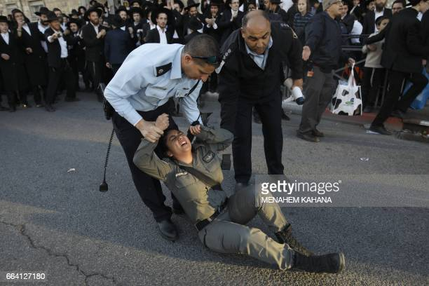 An injured Israeli policewoman is evacuated by comrades after she was ran over by mounted policemen dispersing ultraOrthodox Jews during a protest...
