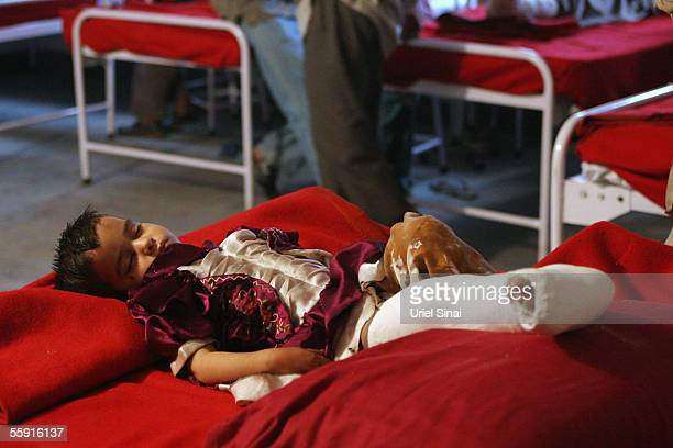 An injured Kashmiri child sleeps on a bed in hospital on October 11 2005 in the mountain village of Kamel Kut in Indian Kashmir India The death toll...