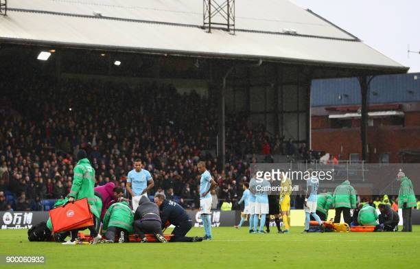 An injured Kevin De Bruyne of Manchester City and Jason Puncheon of Crystal Palace are given assistance during the Premier League match between...