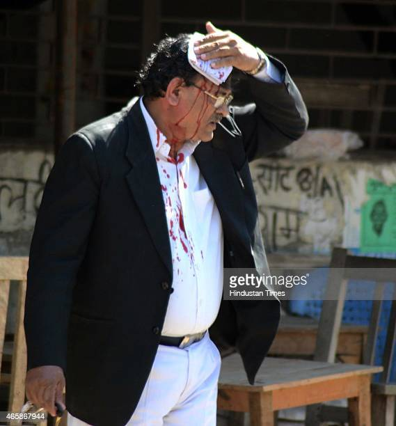 An injured lawyer holding his head to stop the blood during a clash with police outside the district court after a police inspector shot a lawyer in...