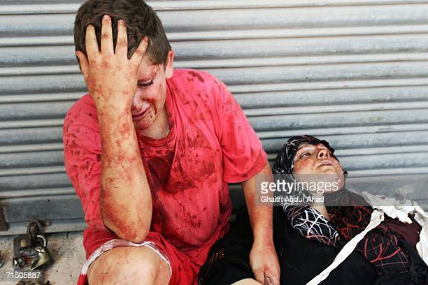 An injured Lebanese boy holds his mothers hand after a rocket from an Israeli aircraft hit their van as they fled their village July 23, 2006 in...