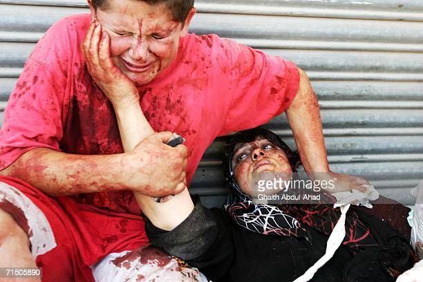 An injured Lebanese boy holds his mothers hand after a rocket from an Israeli aircraft hit their van as they fled their village July 23 2006 in Tyre...
