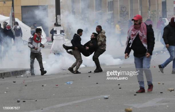 An injured Lebanese protester is carried away as security forces disperse a demonstration in the heart of Beirut to stop a confidence vote for a new...