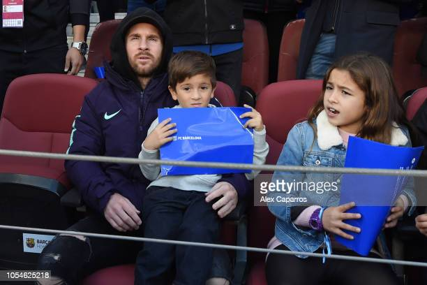 An injured Lionel Messi of Barcelona sits in the stand with son Thiago prior to the La Liga match between FC Barcelona and Real Madrid CF at Camp Nou...