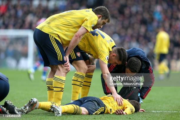 An injured Lucas Torreira of Arsenal is tended to by Sokratis Granit Xhaka and a physio during the Premier League match between Crystal Palace and...