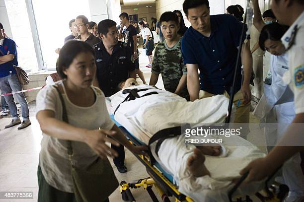 An injured man arrives at the emergency unit of Teda Hospital near the site of a series of explosions in Tianjin northern China on August 13 2015 A...