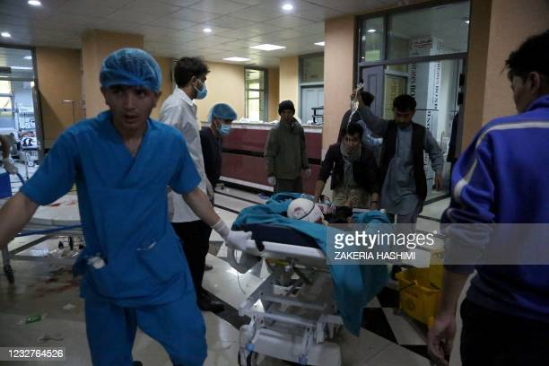 An injured man is being brought on a stretcher to a hospital following a blast outside a school in the west Kabul district of Dasht-e-Barchi on May 8...
