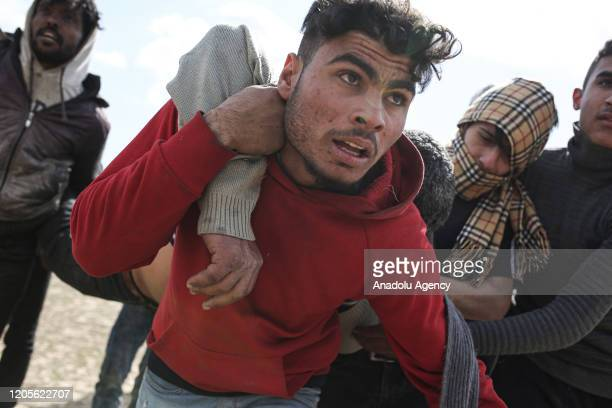 An injured man is carried as Greek security forces use tear gas and water cannon to disperse asylum seekers in the region between the Kastanies and...