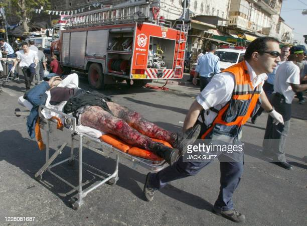 An injured man is carried away after a suicide bomber killed six people in Jerusalem 12 April 2002, and wounded more than 50 others, seven seriously,...