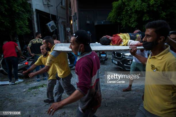 An injured man is carried on a piece of wood after a large explosion on August 4, 2020 in Beirut, Lebanon. Video shared on social media showed a...