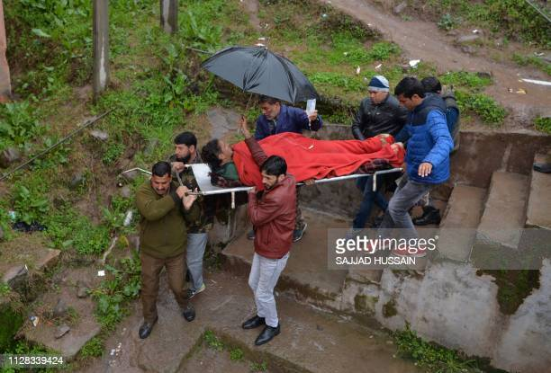 An injured man is carried on a stretcher at a hospital in the Indian Kashmir frontier town of Mendhar on March 2 after being wounded in his home when...