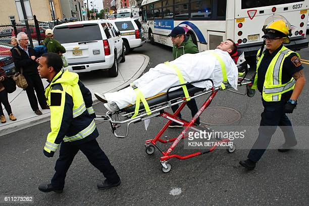 TOPSHOT An injured man is evacuated at New Jersey Transit's rail station in Hoboken New Jersey September 29 2016 A commuter train crashed into a...