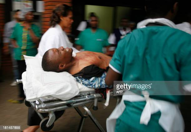 An injured man is wheeled in upon his arrival at the Aga Khan hospital in Nairobi on September 212013 after masked attackers stormed a packed...